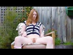 Рыжая девушка снимает себя во время сильного оргазма в саду