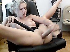 Прелестная блондинка в кресле трахает себя большим резиновым членом