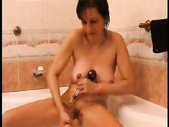 Зрелая женщина удовлетворяет себя вибратором во время принятия ванны