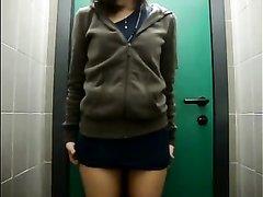 Возбужденная девушка снимает сексуальное напряжение в туалете на работе