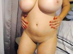 Молодая красотка с большими прекрасными сиськами показывает свое тело и мастурбирует