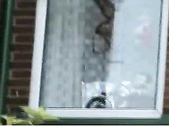 Домохозяйка с маленькими сиськами в видео через окно показывает попку и киску