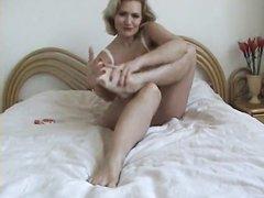 В постели зрелая блондинка в нижнем белье для видео делает домашний фут фетиш