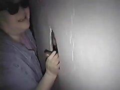 Зрелая толстуха в любительском видео сосёт чёрный член торчащий из дырки в стене