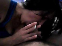 Красивая брюнетка в домашнем видео совмещает курение и сосание большого члена