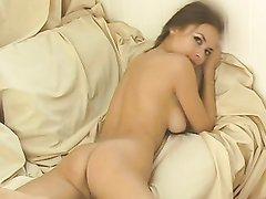 Молодая и красивая леди в любительском видео лежит на диване обнажённой