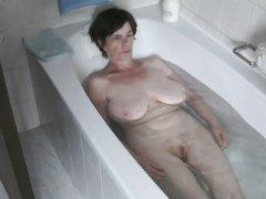 В домашнем видео зрелая и грудастая дамочка разделась и принимает ванную
