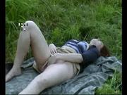 В любительском видео грудастая рыжая женщина дрочит мокрую киску на природе