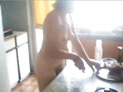 На кухне зрелая домохозяйка с сексуальной фигурой голой готовит блюдо