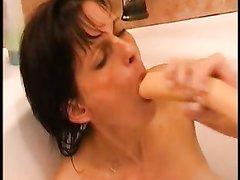 Зрелая домохозяйка в ванной дрочит киску и имитирует минет с большой секс игрушкой