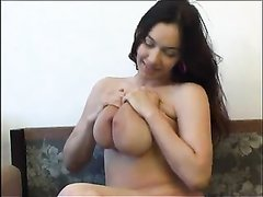 Молодая брюнетка с большими сиськами в домашней соло сцене позирует голой