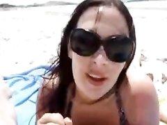 Брюнетка с большими сиськами на пляже строчит любительский минет от первого лица