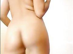 Смуглая брюнетка перед домашней вебкамерой улыбаясь вертится обнажённой
