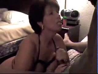 Зрелая дама отсасывая чёрный член радует молодого негра любительским минетом