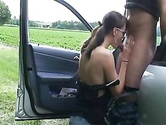Молодая шлюха с трассы встав на колени делает любительский минет водителю