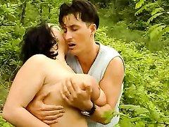 Зрелая толстуха с большими сиськами на природе трахается с молодым любовником