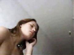 Рыжая проститутка в постели ублажает клиента делая любительский минет