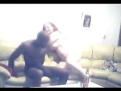 Рыжая домохозяйка сосёт чёрный член и на диване ублажает возбуждённого негра