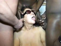 Грудастая зрелая брюнетка сосёт чёрные члены для группового окончания на лицо