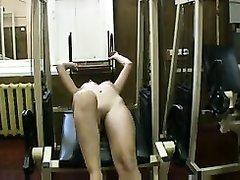 Молодая брюнетка с маленькими сиськами в спортзале тренируется обнажённой
