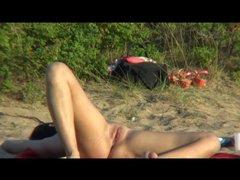 Брюнетка с бритой киской на нудистском пляже загорает перед скрытой камерой