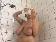 Возбуждающая красотка с натуральными огромными сиськами принимает душ