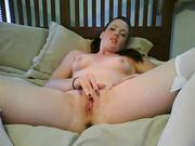 Рыжая девушка с татуировкой раздевается и мастурбирует лежа