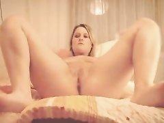 Широкобёдрая блондинка пальчиками мастурбирует бритую киску в постели
