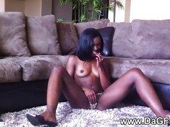 Длинноногая негритянка сидя на полу мастурбирует шоколадную киску пальчиками