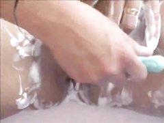 Зрелая грудастая брюнетка в ванной крупным планом бреет волосатую киску