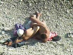 На пляже любительская скрытая камера снимает возбуждённую зрелую пару