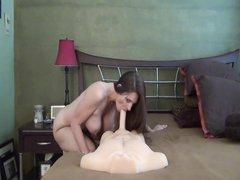 Грудастая молодая девушка раздевшись мастурбирует киску с помощью фаллоса