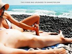 На пляже грудастая брюнетка дрочит член любовника перед скрытой камерой