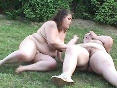 Очень толстые, заплывшие жиром лесбиянки на зелёной полянке разминаются и приступают к сексу