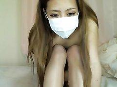 Японская студентка в медицинской маске сидит голая перед вебкамерой и руками трогает сиськи