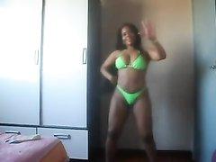 Фигуристая негритянка в салатовом купальнике ритмично танцует и нагнувшись вертит попой бесплатно