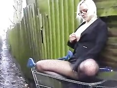 Очкастая блондинка в колготках, желая секса залезла в магазинную тележку и перед парнем трахает киску дилдо