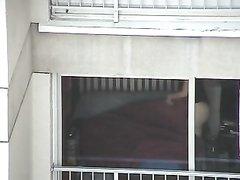 Из дома напротив одинокий мужик подглядывает через окно за фигуристой дамой, расхаживающей дома в чёрных стрингах