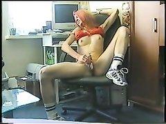 Рыжая домохозяйка трахает киску дилдо возле компьютера, она возбудилась после порно и решила кончить