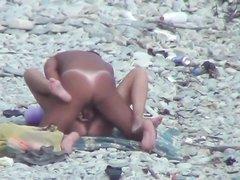 Загорелая пара на каменистом пляже увлечена сексом на радость любителю подглядывать, установившему скрытую камеру