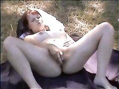 Русская девушка из деревни на природе легла на свою одежду и балуется с секс игрушкой, желая оргазм и успокоения