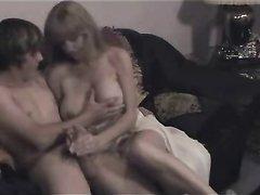 Для домашнего секса зрелая красотка пригласила молодого и стеснительного студента, усадив его на диван взяла его за член
