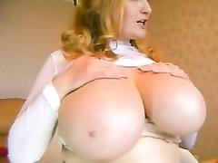 Упитанная леди с огромными сиськами щупает их напоказ и зажимает между ними секс игрушку, она настоящая прелесть