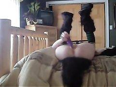 Распутная девушка в странной обуви лежит на спине с задранными ногами и фиолетовой секс игрушкой доводит себя до оргазма