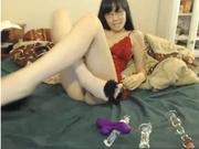 На вебкамеру очкастая азиатка долбит секс игрушками рот и киску, а в попу суёт пальчик