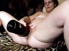 Любительское видео со зрелой домохозяйкой, которая использует бутылку для интимной долбёжки растянутой киски