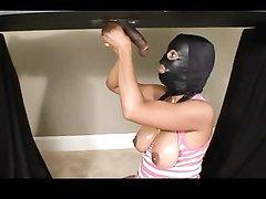 В любительском порно зрелая брюнетка с косами надела маску и сосёт чёрный член под столом через дырку