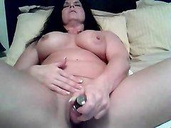 Мастурбация с секс игрушкой от зрелой брюнетки с большими сиськами, лежащей в постели перед вебкамерой