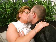 Зрелая и жирная дама в очках в домашнем видео ублажает молодого бездельника
