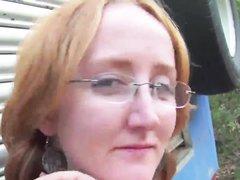 Зрелая интеллигентка в очках на улице показывает для видео рыжеволосую киску